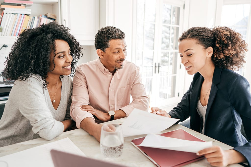 Three people looking over contract