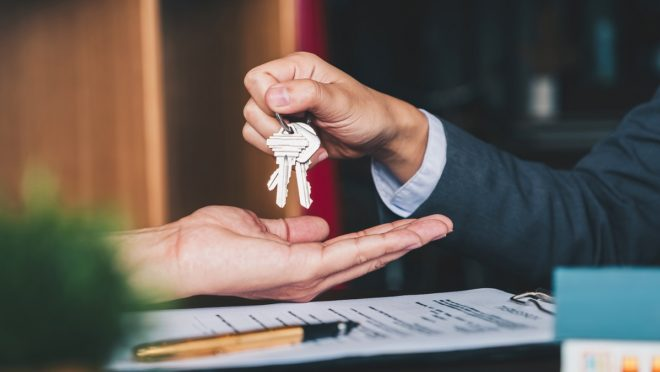 Person handing over the keys to their house