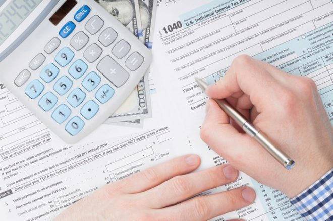 Person filling out a 1040 tax form with calculator and money nearby.