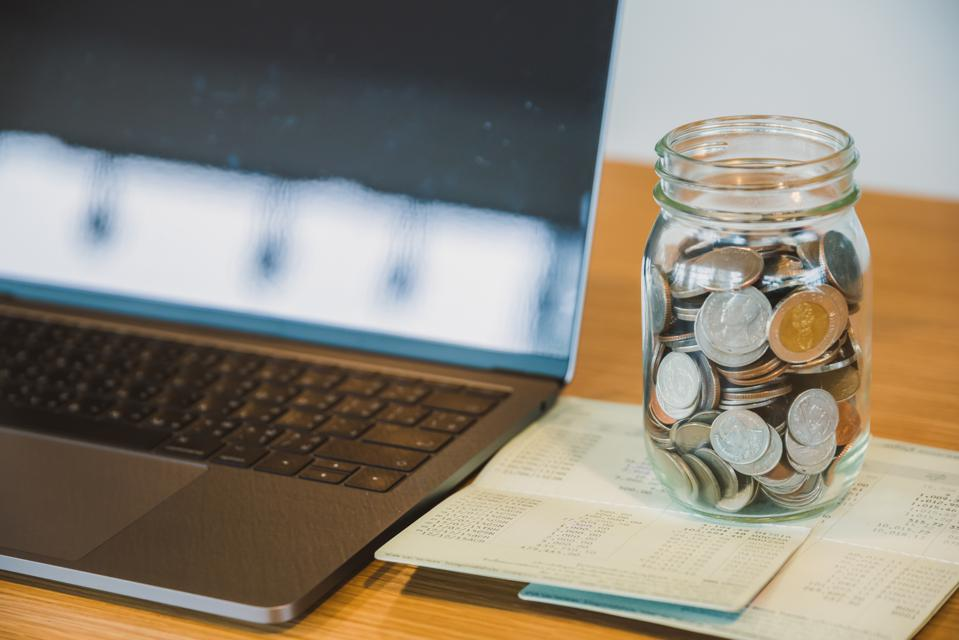 Close-Up Of Coins In Jar By Laptop On Table